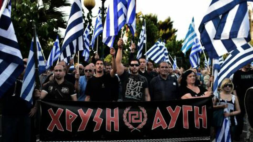 STØTTE: Greske flagg og logoen til partiet Gyllent Daggry. Foto: AFP PHOTO / ARIS MESSINIS