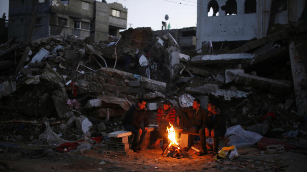 <strong>UTEN HJEM:</strong> Palestinere på Gaza varmer seg på et bål utenfor ruinene av et hus i desember, som vitner sier ble ødelagt av israelske bomber under den 50 dager lange krigen i fjor sommer. Foto: REUTERS / Mohammed Salem