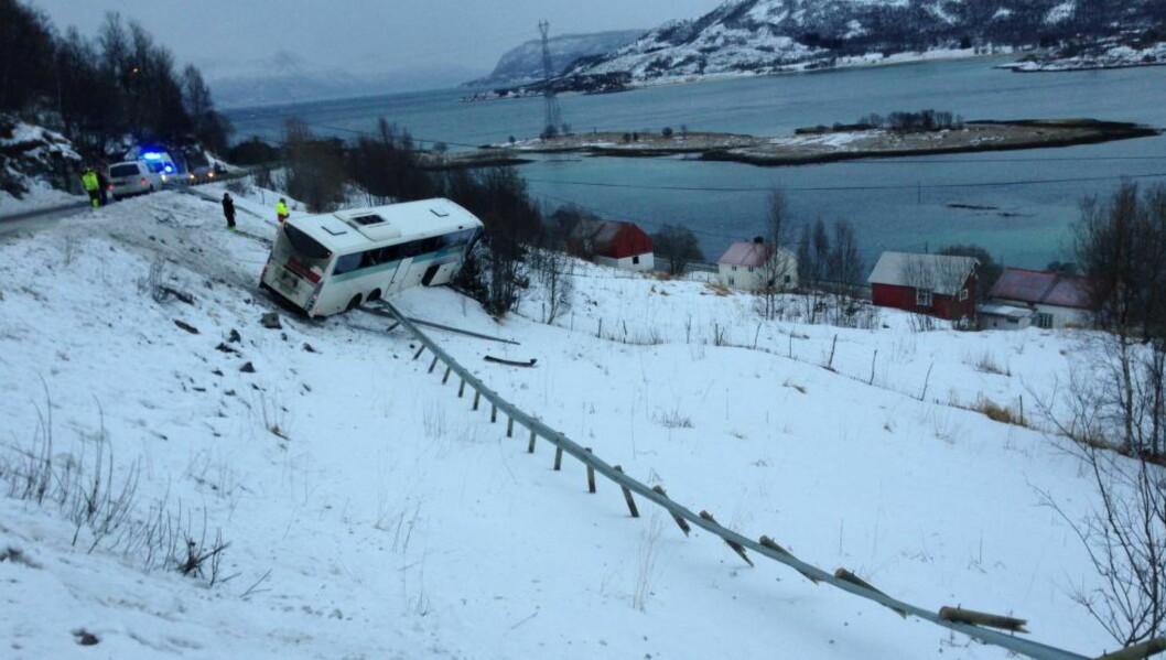 <strong>STO I FARE FOR Å TIPPE:</strong> Ingen ble alvorlig skadd da denne bussen kjørte ut av veien ved Tjeldsundbrua utenfor Harstad i dag. Alle på bussen kom seg til slutt ut og bussen tippet ikke. Foto: Marcus Nilssen