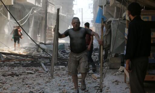FLYKTER FRA BOMBENE: En syrisk mann flykter fra bombene i det nordlige Aleppo. Bildet er tatt den 15. august i år. Foto: AFP PHOTO / AMEER ALHALBI/ NTB Scanpix
