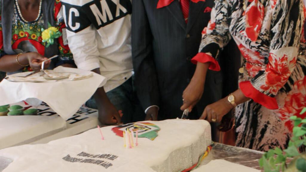 AFRIKA-KAKE: Grace Mugabe hjelper sin mann Robert Mugabe (i midten) med å kutte bursdagskake. Foto: Reuters / NTB scanpix