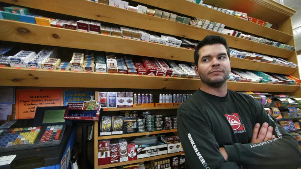 TOBAKKSSALG:  Brian Vincent driver en familieeid dagligvarebutikk på Main Street i Westminster. Han forteller at tobakksprodukter utgjør mer enn fem prosent av salget i butikken. Dermed vil han bli hardt rammet av en eventuell lovendring. Foto: AP.