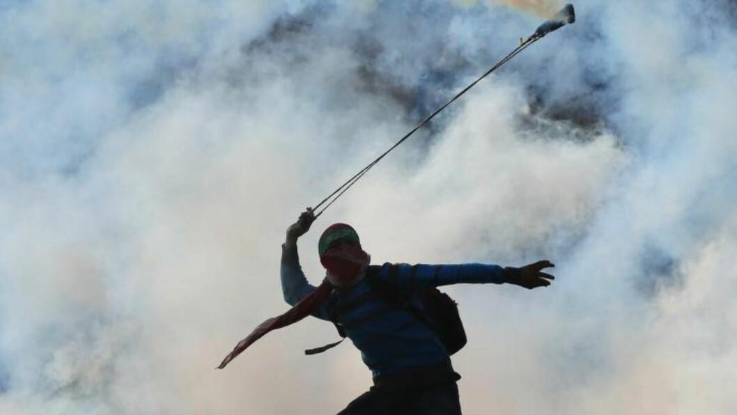 <strong>SPENT STEMNING:</strong>  En maskert palestiner kaster en tåregassgranat tilbake mot de israelske soldatene som akkurat har sendt dem mot de steinkastede palestinere utenfor Ofer-fengselet, nær Ramallah. Gårsdagens angrep i en synagoge i Jerusalem har gjort stemningen i det både Israel og palestinerne vil ha til sin hovedstad enda mer spent. Foto: Abbas Momani/Afp/Scanpix