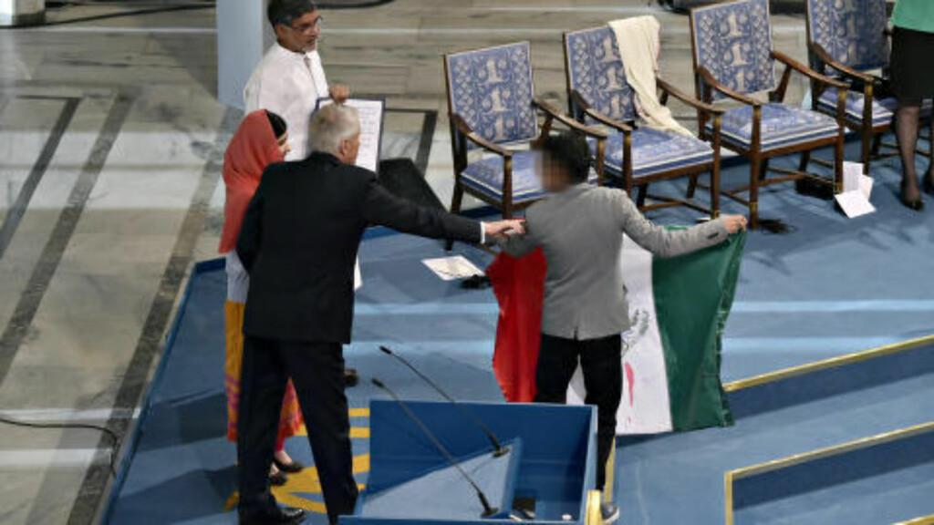 DRAMATIKK: Her tar Torbjørn Jagland tak i den unge mannen som kom opp på scena med det som ser ut som et meksikansk flagg. Foto: Hans Arne Vedlog  / Dagbladet