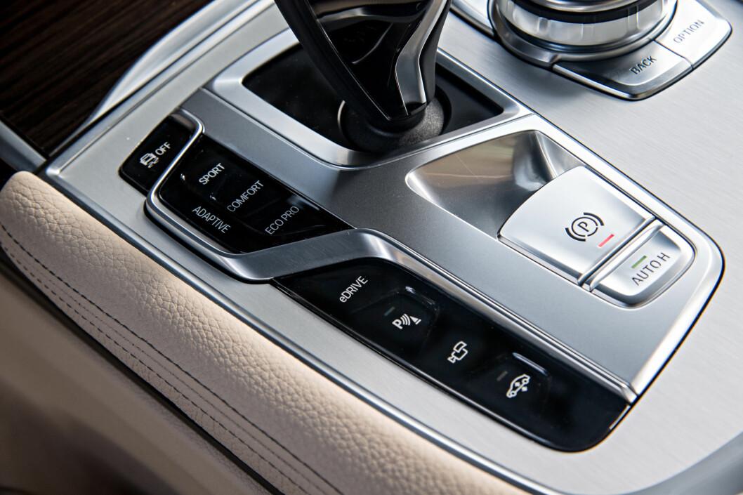 <strong><b>FØREREN VELGER:</strong></b> Til venstre for girspaken finnes e-Drive-knapp, som gir tilgang til hybrid-innstillingene via instrumentpanelet. Lenger frem ligger Driving Experience Control-bryteren, der man velger mellom innstillingene Sport, Comfort, Adaptive eller EcoPro (økonomisk). Nærmest ligger innstillingene for parkeringsvarler, kamerafunksjon og høydeinnstilling av luftdemingen. Foto: BMW