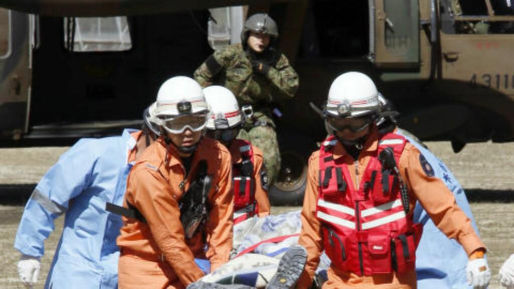REDDET:  Redningsmannskaper frakter en av de overlevende i sikkerhet. Foto: NTB SCANPIX