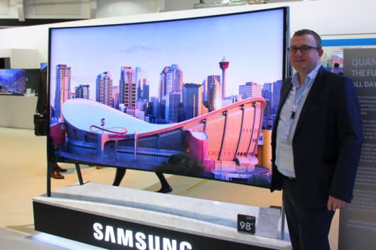 <strong><B>ALENE OM BUE</B>:</strong> De fleste produsentene har kuttet ut buede TV-er, men Samsung har fortsatt noen modeller. Her viser Samsungs Knut-Eirik Rørnes frem en 98-tommer fra årets kolleksjon. Foto: BJØRN EIRIK LOFTÅS