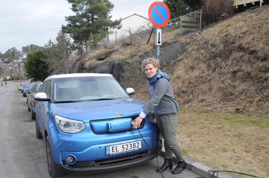 <strong><B>LADER I SMUG:</strong></B> Gro Rebnord må feilparkere bilen og strekke ledning ut av vinduet på leiligheten sin for å få ladet elbilen sin. Foto: TORE NESET