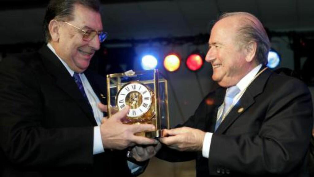 EN KLOKKENES MANN: Joseph Blatter, som han egentlig heter, gir her en sveitsisk klokke til Paraguays fotballpresident OScar Harrison i anledning hundreårsjubileet deres i 2006. Trøbbelet Blatter slev befinner seg i nå, er derimot rundt en klokke han selv fikk under sommerens VM. Foto: AP /Jorge Saenz / NTB Scanpix