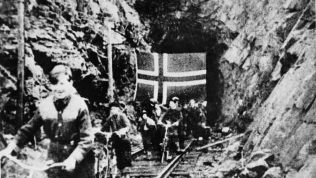 FRIGJORT: Sivile som har skjult seg i gruvegangene i Bjørnevatn gruver i Kirkenes, kommer lykkelige ut med flagg under frigjøringen og møter de sovjet-russiske soldatene fra Den røde arme. Foto: NTB scanpix