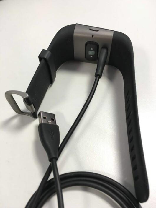 <strong><b> LADE:</strong> </b> Ladekabelen til Fitbit Surge er enkel å bruke, men sitter kanskje litt løst i klokka. Man må passe på at den faktisk lader.  Foto: HANNA SIKKELAND