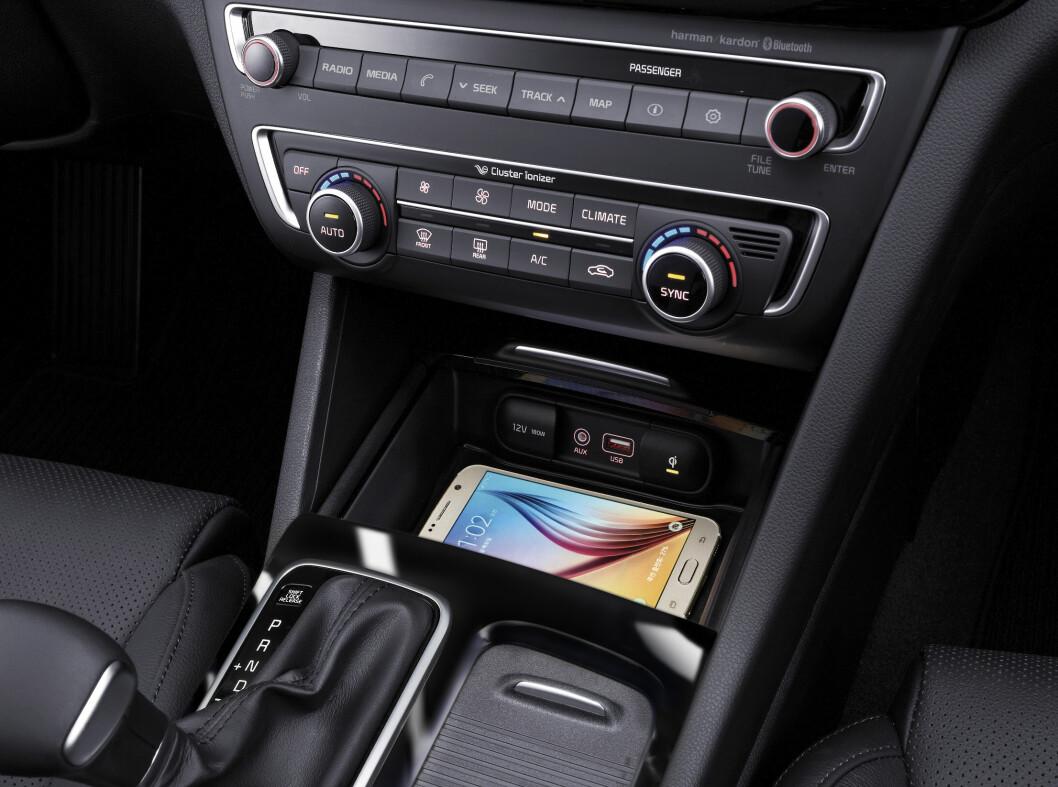 <strong><b>MED LADER I MIDTKONSOLLEN:</strong></b> kan du enkelt lade telefonen mens du kjører uten å klusse med ledninger. Bilen sier også ifra om du glemmer den når du stopper.   Foto: KIA
