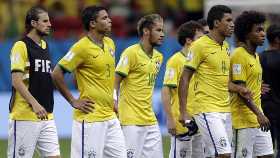 <strong>DEPPET:</strong>  De brasilianske spillerne med Neymar i spissen var ikke spesielt høye i hatten da de gikk av banen i natt. FOTO: NTB SCANPIX