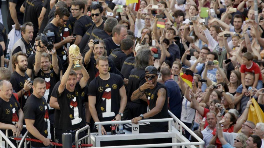<strong> GOD STEMNING:</strong>  Thomas Müller viser fram VM-pokalen til det tyske folk fra bussen som frakter de gjennom Berlin. Foto: AP Photo/Michael Sohn