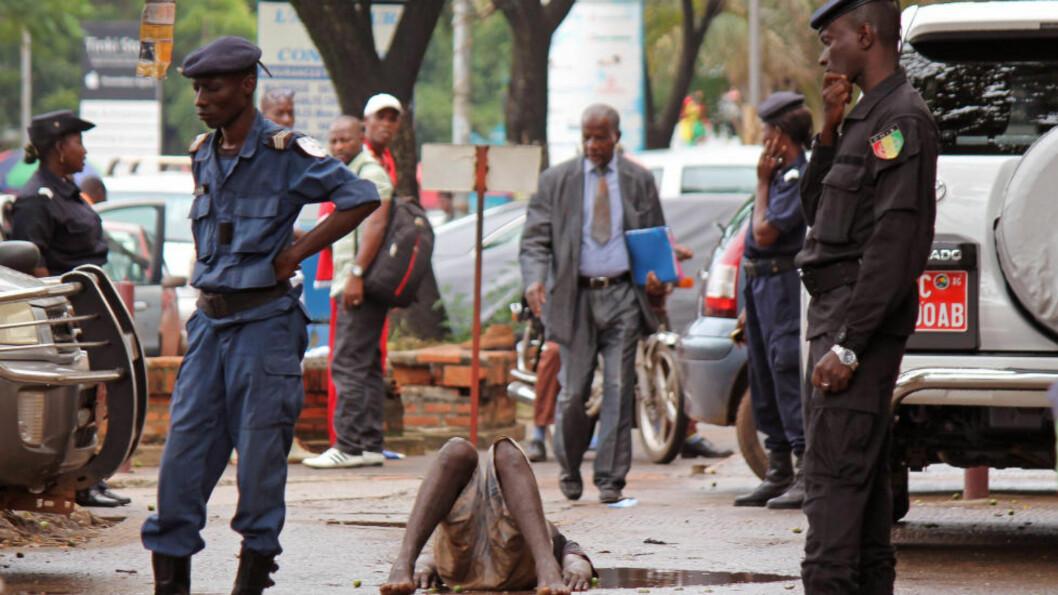 <strong>EBOLA-PANIKK:</strong> En mann segner om på gata i byen Conakry i Guinea, og frykten for ebola gjør at politifolk straks sikrer området rundt den syke mannen. Han skal ha blitt liggende på gata i flere timer før han omsider ble fraktet til et eget ebola-senter for undersøkelser. Foto: AP Photo/ Youssouf Bah