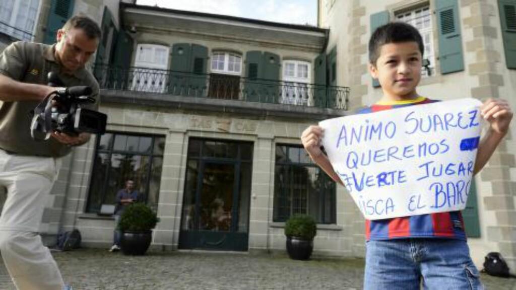 BARCA-ANKE: Barcelona-supportere verden rundt håper Suarez lykkes. Det gjelder også 10-årige Carlos som holdt opp en plakat i Lausanne i dag, med følgende budskap: «Suarez, vi ønsker å se deg spille for Barca». Foto: EPA / LAURENT GILLIERON / NTB SCANPIX