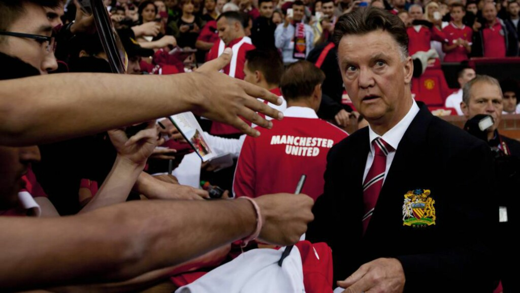 Manchester United's new manager Louis van Gaal, right, signs autographs as he takes to the touchline before his team's pre season friendly soccer match against Valencia at Old Trafford Stadium, Manchester, England, Tuesday Aug. 12, 2014. (AP Photo/Jon Super) / TT / kod 436
