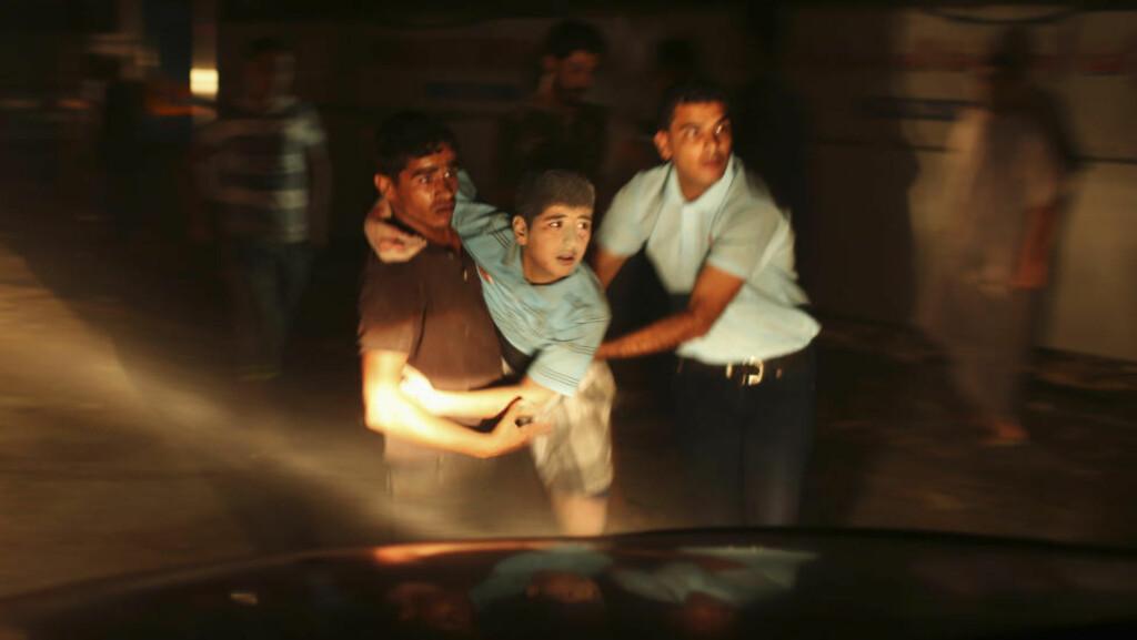 KRIGENS OFFER: En palestinsk gutt, såret i et israelsk luftangrep mot Gaza i dag, fraktes bort av medhjelpere. En kvinne og ei toårig jente ble de første dødsofrene etter at fredsforhandlingene i Kairo brøt sammen tidligere i dag. Foto: MOHAMMED SALEM / REUTERS / NTB SCANPIX
