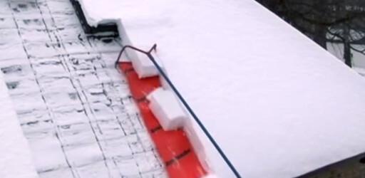 PLASTHJELP: Snøen skjæres med rammen og sklir av taket på plaststykket. Foto: PRODUSENTEN