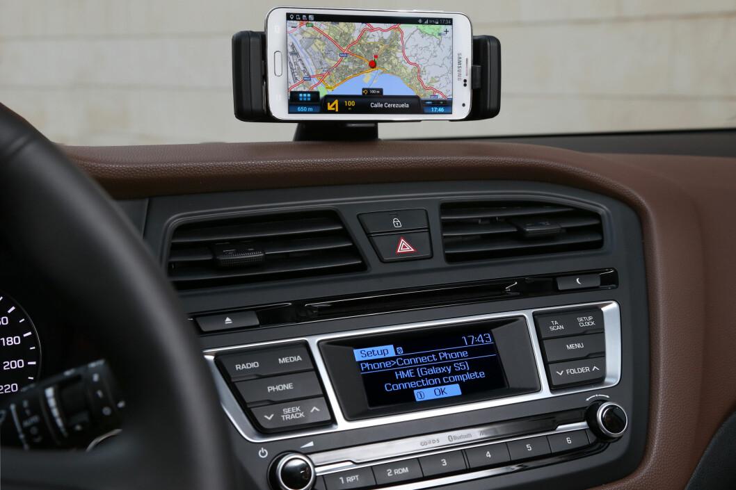 <strong><b>SATSER PÅ MOBILEN:</strong></b> i20 leveres med docking for mobil. De mener kundene heller ønsker å bruke den istedet for integrerte løsninger i billigbiler. Foto: HYUNDAI