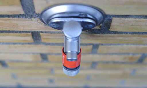 image: Koblingen til hageslangen kan føre til vannskader i veggen om du ikke tar den av