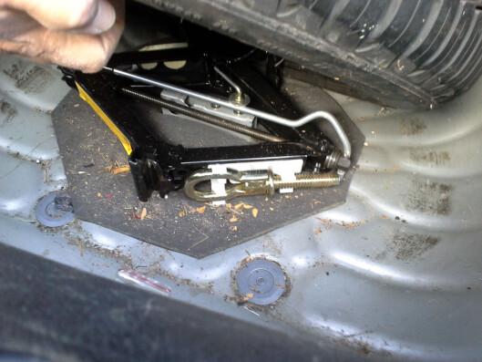 <strong><b>Trinn 3:</strong></b> Tauekroken ligger ofte sammen med reservehjul/ reservehjulssettet. Det beste er imidlertid å ha den i hanskerommet. Foto: FALCK