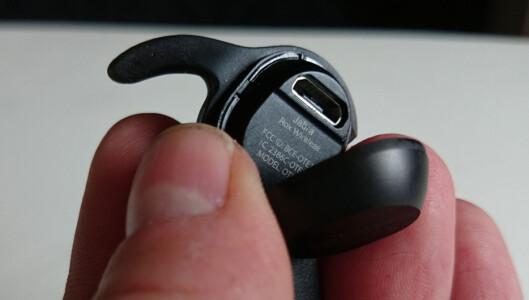Porten for å lade finner du bak et lokk på den venstre øreproppen.