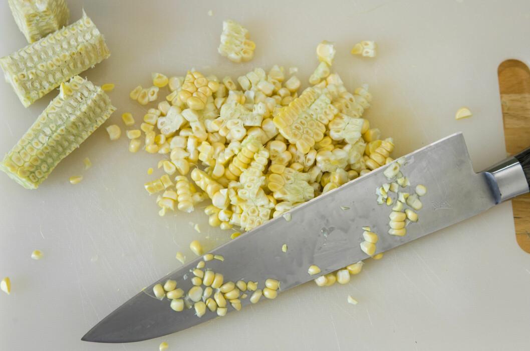 Skjær av maiskornene, så trenger du ikke store gryten for å dampe dem. Og deler du kolben i to-tre stykker først, slik som på bildet over, unngår du maiskorn over <i>hele</i> kjøkkenet. Foto: Per Ervland