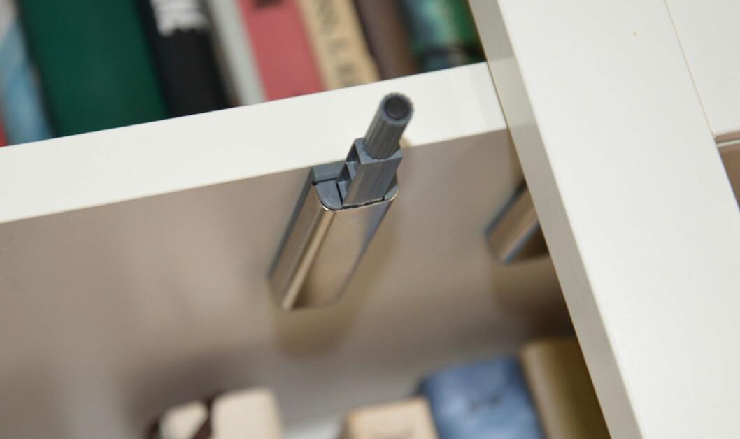 Dørene åpnes ved å trykke karmen inn, da spretter den opp ved hjelp av denne mekanismen. Foto: Brynjulf Blix