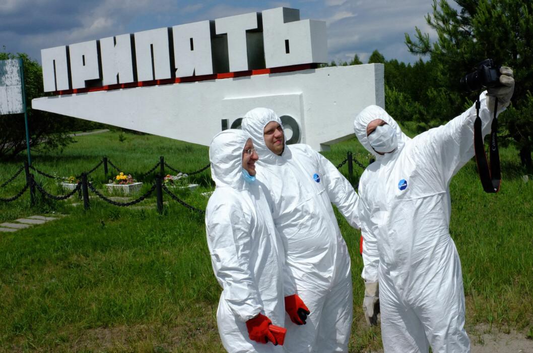 <strong>IKKE SYDEN:</strong> Her har en gruppe russisktalende turister ikledd seg fullt beskyttelsesutstyr utenfor skiltet som ønsket Tjsernobyl-arbeider velkommen til Pripjat. Neppe nødvendig, men artig på bilder. Foto: Ole Petter Baugerød Stokke
