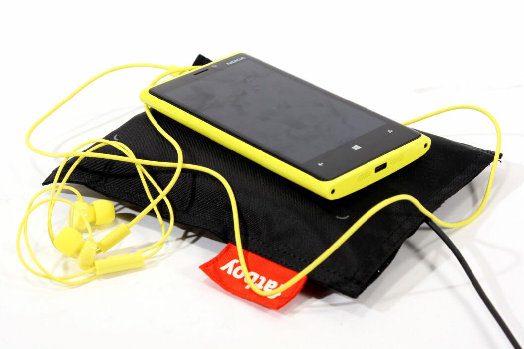 <strong>PUTEKOS:</strong> Nokia Lumia 920 kan legges ned på ladeputer som denne, for å lade trådløst. Merk også de matchende ørepluggene, som følger med mobilen.  Foto: Ole Petter Baugerød Stokke