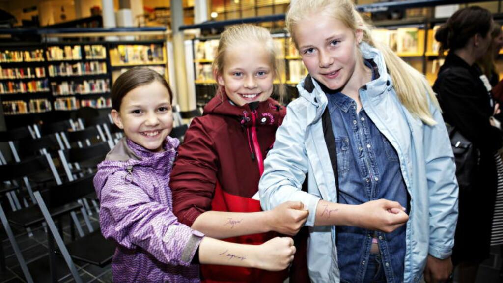 INGVAR PÅ ARMEN: Oda Bakken Engen (11), Emma Sagdalen (12) og Erle Fangel (12) sikret seg forfatterens autograf. Foto: Nina Hansen / Dagbladet