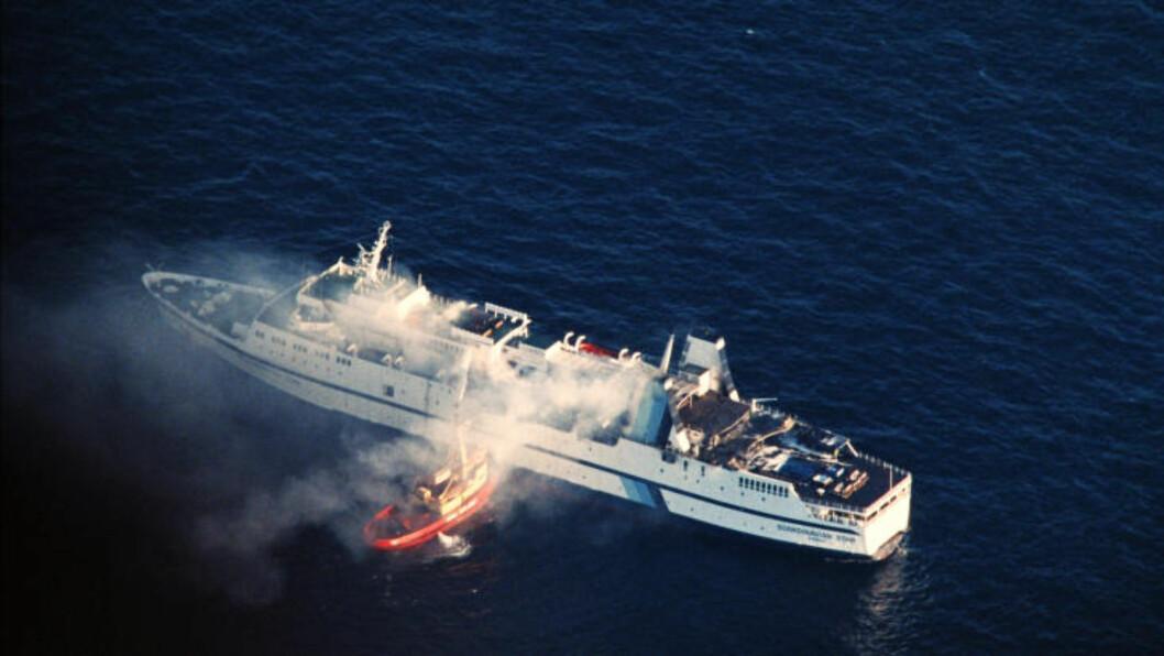 <strong>TRAGEDIE:</strong> På dette bildet, tatt 8. april 1990, driver brannmannskaper slokkearbeid på havaristen «Scandinavian Star» i Skagerrak. 159 mennesker døde i brannen. Foto: JOAKIM ROOS / AFP / NTB SCANPIX