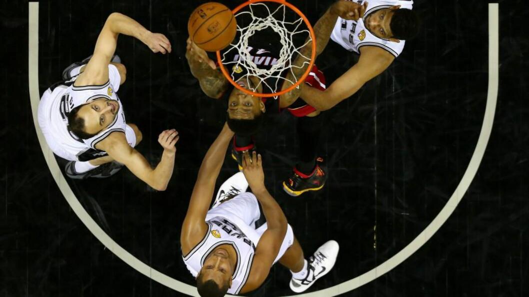 <strong>OVENPÅ:</strong> Udonis Haslem fra Miami Heat rister av seg tre Spurs-spillere i finalen i natt og setter to poeng, men det var ikke nok mot de nybakte NBA-mesterne.Foto: Andy Lyons/Getty Images/AFP/ NTB Scanpix