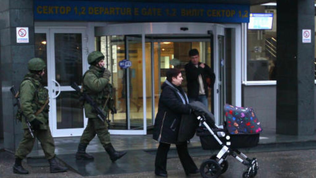VÆPNET KONTROLL:  Vaktene, som nå er bekreftet som russiske soldater, holder kontroll ved inngangen til flyplassen i Simferopol fredag morgen. Foto: REUTERS/David Mdzinarishvili/NTB Scanpix.