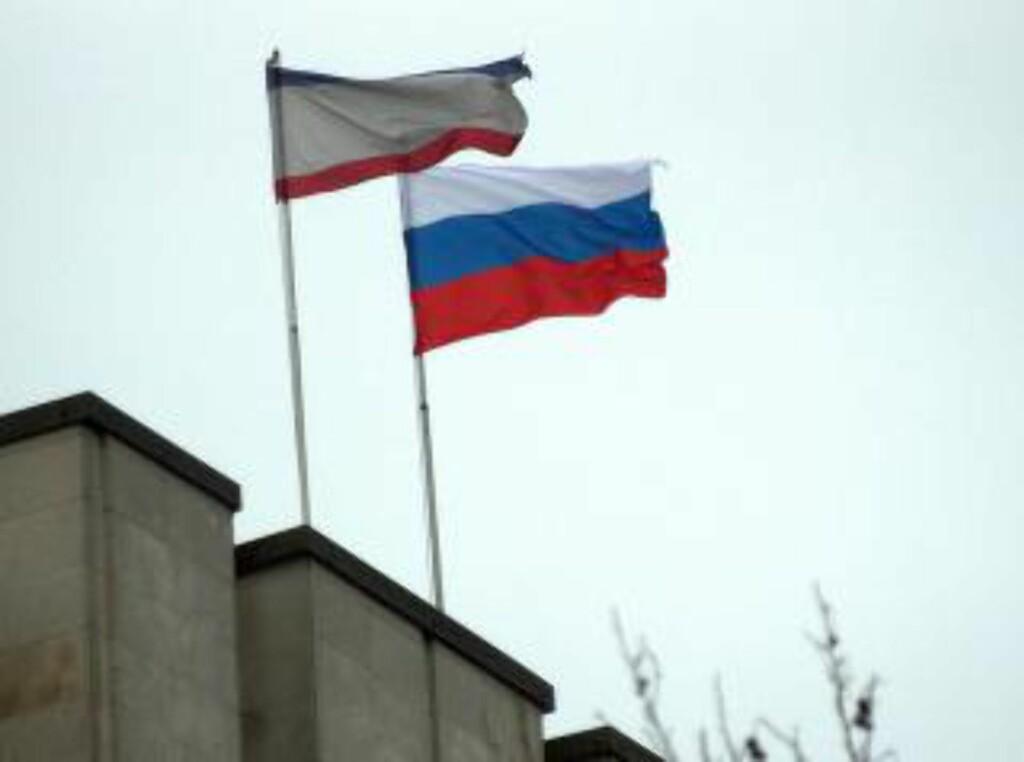 RUSSISK FLAGG:  Både et russisk flagg og et regionalt Krim-flagg er nå heist på parlamentsbygningen i Simferopol i Ukraina, der russiske soldater natt til fredag tok kontroll over flyplassen. Foto: Vasilij Batanov, AFP/NTB Scanpix.