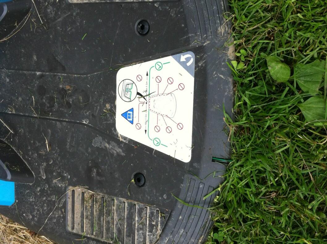 Til venstre foran klistremerket ser du den grønne ledekabelen. Uten denne på plass vil ikke Gardenaen klare å finne veien tilbake til dokkingstasjonen.  Foto: Øyvind P