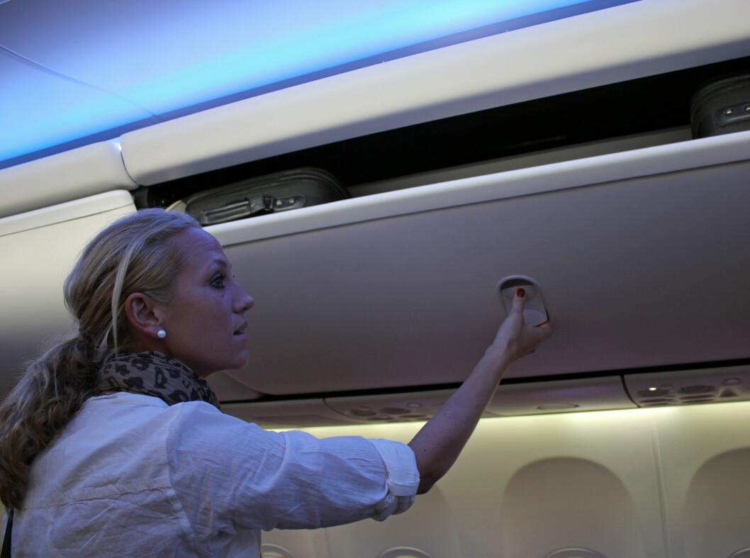 En flyvertinne viser hvordan hattehyllen enkelt kan åpnes fra undersiden. Foto: Silje Ulveseth