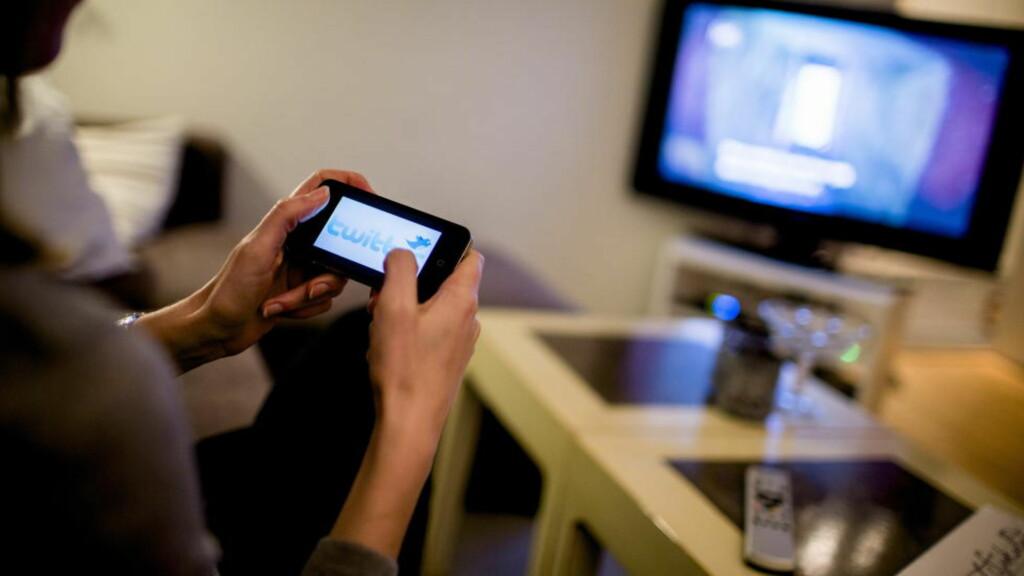 SOSIALE MEDIER: To av tre nordmenn bruker sosiale medier hver dag. Her en dame som tvitrer mens hun ser på TV. Foto: Stian Lysberg Solum / NTB scanpix