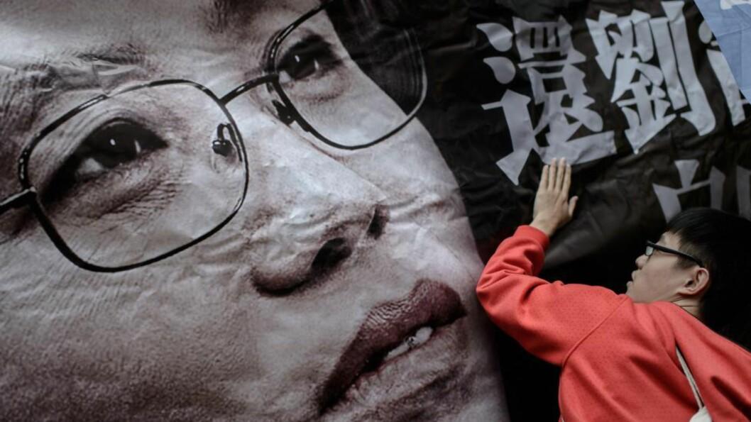 <strong>GLEMMES IKKE:</strong> En demonstrant i Hongkong klistrer opp en plakat med bilde av Liu Xia, kona til den fengslede freddsprisvinneren Liu Xiaobo. Liu Xia sitter i husarrest med alvorlige hjerteproblemer. Foto:  AFP / NTB Scanpix