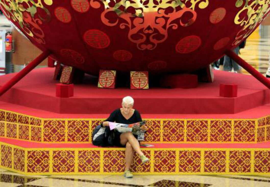 <strong>DEKORASJON:</strong> En reisende sitter under en dekorasjon i forbindelse med kinesisk nyttår på flyplassen i 2010.Foto: Wong Maye-E/AP/NTBScanpix