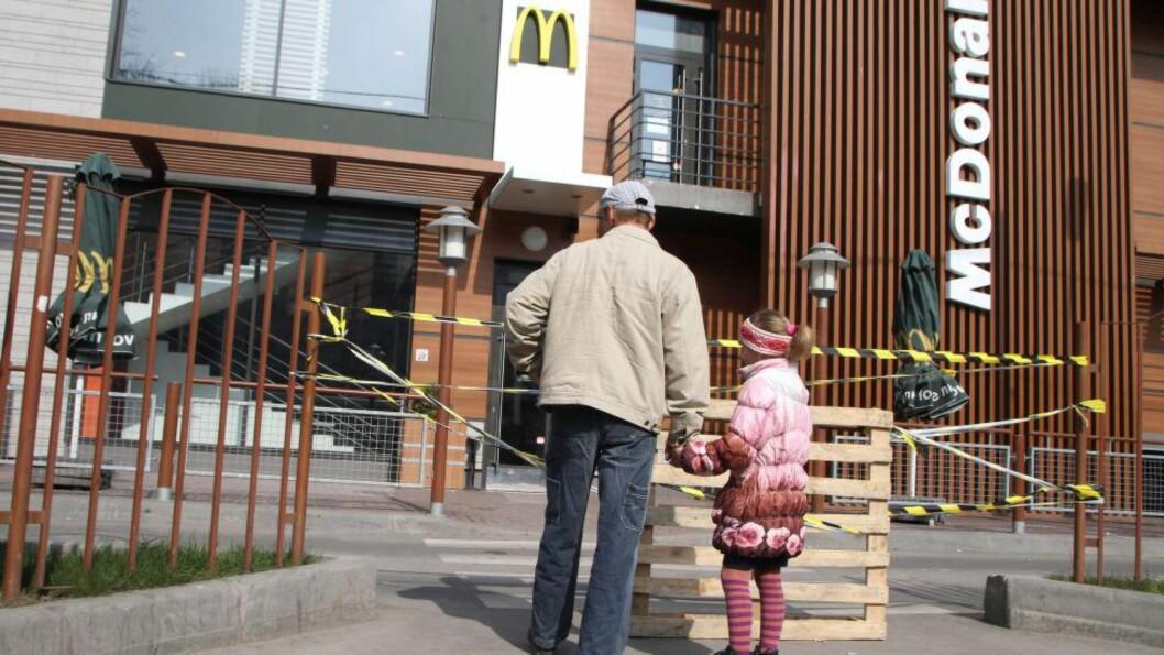 <strong>STENGT:</strong> McDonald's-kjeden har stengt sine restauranter på Krim-halvøya. Her står to kunder utenfor hamburgergigantens serveringssted i Simferopol. Foto: AFP PHOTO/ YURIY LASHOV
