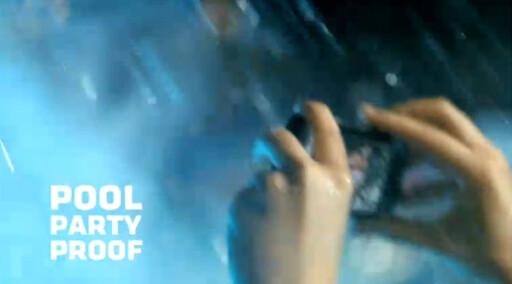 """REKLAMER: Motorola bruker aldri ordet vanntett (water proof) om Defy. Men de bruker blant annet """"pool party proof"""", og viser hvordan den kan bli splasjet full av vann. Foto: Skjermdump fra Youtube"""
