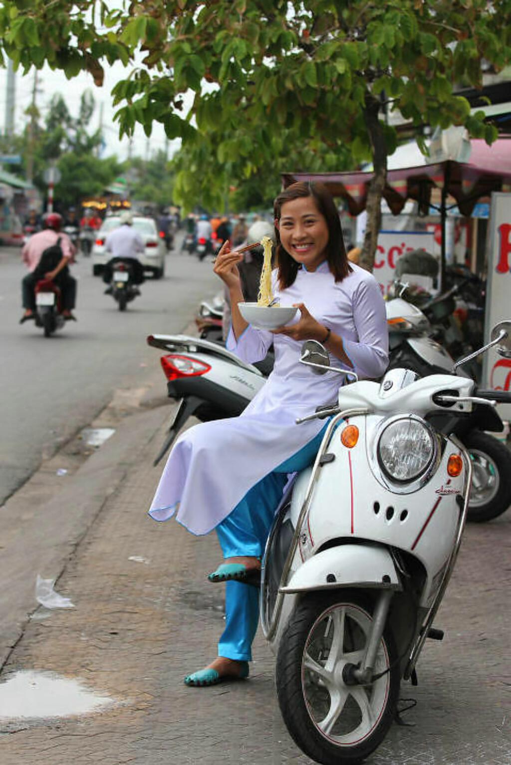 VISER HEMMELIGHETENE: Nguyen Ho Minh Thu bruker scooteren til å vise turistene stedene og gatematen du aldri ville funnet fram til på egen hånd. Foto: RUNAR LARSEN