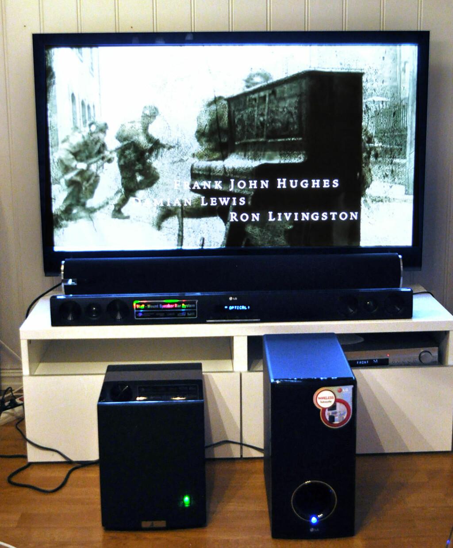 Her er de to plankene på plass foran TV-en, med sine respektive trådløse subwoofere. Sub til venstre fra Arvani, LG til høyre. Foto: Bjørn Eirik Loftås