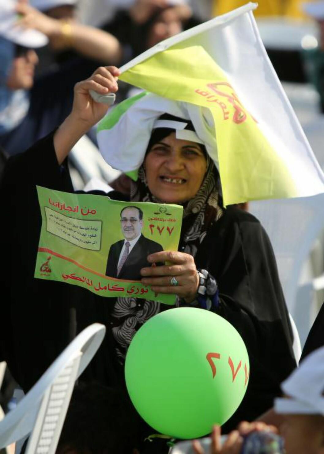 <strong>SKAL STEMME:</strong>  En irakisk kvinne holder oppe en plakat av den irakiske statsministeren Nuri al-Maliki i Bagdad i helga. Det er forventet at Maliki vil beholde sin statsministertittel etter valget til tross for kaos, korrupsjon og kritikk. Foto: Ahmad al-Rubaye/Afp/Scanpix