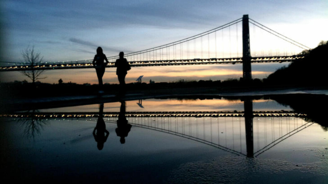 FILE - In this Nov. 26, 2011 file photo two women walk at Palisades Interstate Park as the sun sets over the George Washington Bridge, in Fort Lee, N.J. Many people have known little about Fort Lee until a political scandal centering on New Jersey Gov. Chris Christie enveloped the borough. Now for residents of the New York City bedroom community defined by both a feisty pride and frustration over the mixed blessings of proximity to the George Washington Bridge, the scandal is the reminder they did not need of how the bridge dictates the rhythm of everyday life. (AP Photo/Julio Cortez, File)