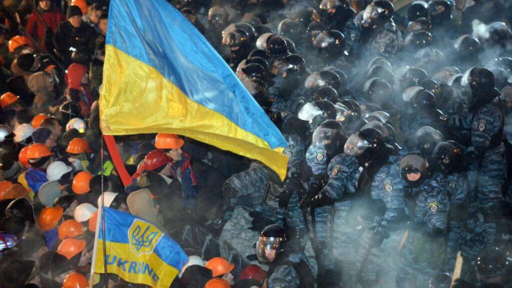 STORMET FRIHETSPLASSEN: Her stormer det ukrainske elitepolitiet «Berkut» Frihetsplassen i sentrum av Kiev 11. desember, selve episenteret for opprøret som nå brer om seg i Ukraina. Mange reagerer på at den brutale sikkerhetsstyrken, som har et mandat fra Innenriksdepartementet om å håndtere farlige og voldelige hendelser i forbindelse med store folkemengder, ble satt inn mot i utgangspunket fredelige demonstranter. Innledningsvis dreide protestene seg om et krav til president Viktor Janukovitsj om å si ja til en avtale med EU. Etter hvert som spenningen har økt og volden tiltatt, er hovedparolen nå at Janukovitsj må gå av. Foto: SERGEI SUPINSKY / AFP PHOTO