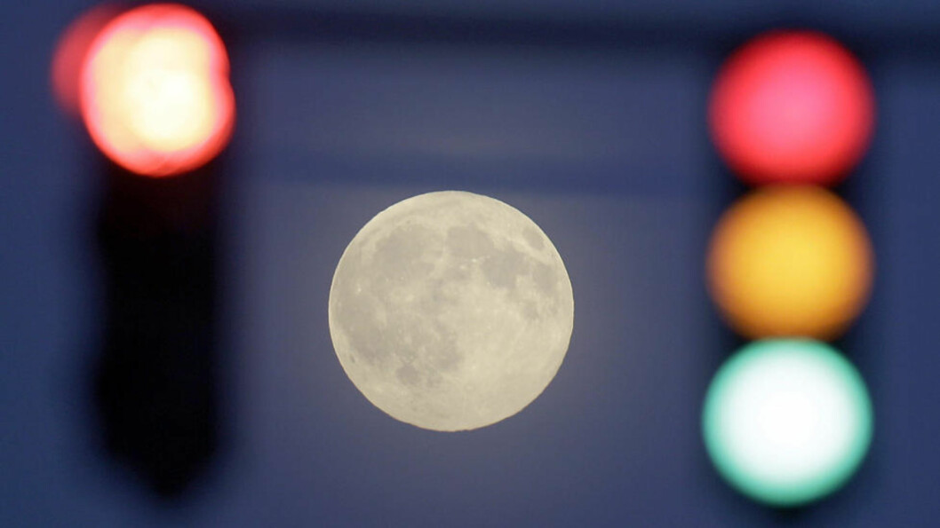 The full moon is seen in Duisburg behind traffic lights during clear and cold weather. Weather forecasters predict subzero temperatures for the end of the week in Germany. (AP Photo/Frank Augstein)