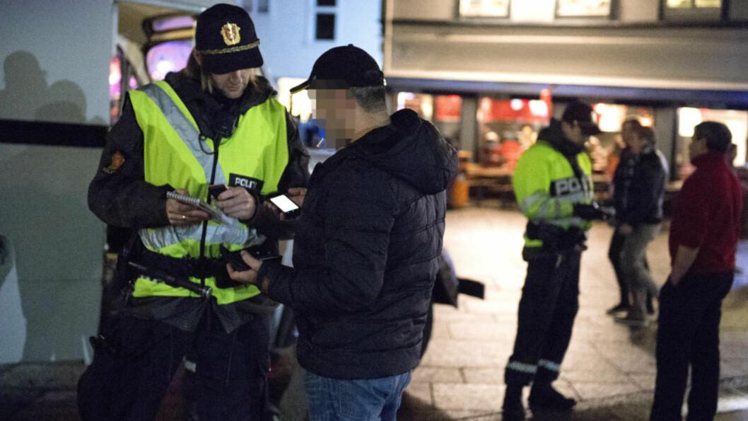 <strong>SJEKKER PAPIRENE:</strong> Stavanger-politiet sjekker ID-papirene til ansatte ved én av Stavangers mange gatekjøkkener. Foto: Øistein Norum Monsen